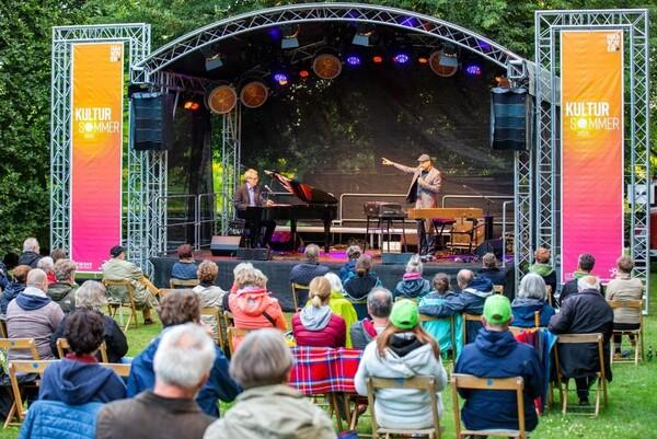 Auf einer mit Kultursommer-Flaggen eingefassten Open-Air-Bühne spielt ein Pianist und ein Mann steht mit einem Mikro und zeigt zu ihm, davor sitzt Publikum auf Klappstühlen © Ines Schiermann