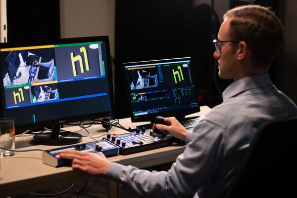 Vor einem großen und einem kleinere Bildschirm auf dem das h1-Logo zu sehen ist, sitzt ein Mann und bedient die Gerätschaften © h1