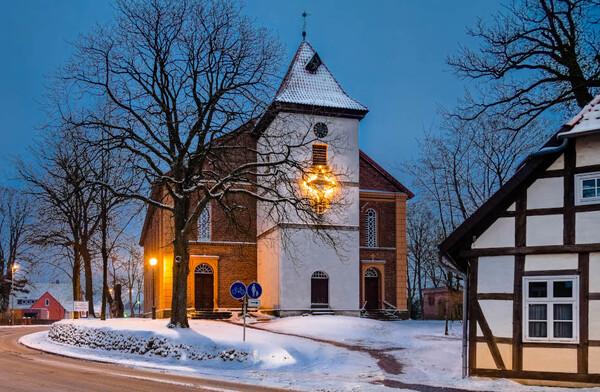 Eine große Kirche in einer winterlichen Dorflandschaft mit Fachwerkhaus © Hans-Jürgen Weiß